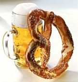 A salt pretzel beside a litre of beer