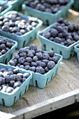 Blueberries in paper dishes on a wooden table
