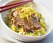Beef with sesame crust on leeks and noodles