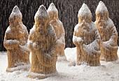 Weihnachtsmänner aus Rührteig stehen im Puderzuckerschnee