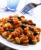 Noodles with sausages and black olives