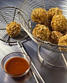 Fish balls with nut crust, chili dip beside them