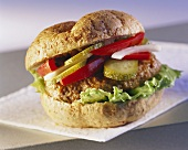A hamburger with gherkin and peppers