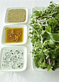 Three different salad dressings beside mixed salad leaves