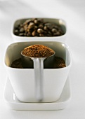 Coffee powder with spoon and coffee beans in bowls