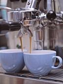 Cappuccino fliesst durch die Maschine in zwei Tassen