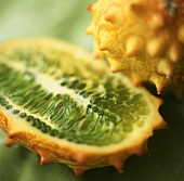 Half and whole kiwano on a green background