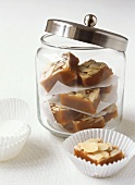 Toffee and almond slices in a jar and in front of it