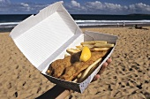 Hand holding fish and chips in a carton at the seaside