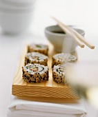 Sesame sushi on a wooden board, soya dip behind