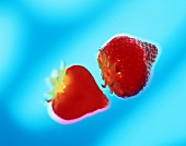 Two strawberries against blue background (surreal)