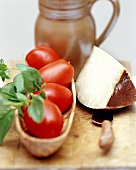 Fresh tomatoes, basil and piece of cheese; terracotta jug