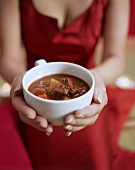 Woman in red dress serving Hungarian goulash soup