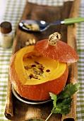 Creamed pumpkin soup with pumpkin seeds in hollowed-out pumpkin