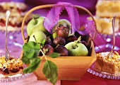 Pieces of apple cake and plum cake, fruit basket between them