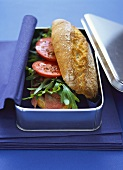 Baguette with pastrami, rocket and tomatoes in picnic box