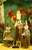 Various bottles of olive oil on table in garden
