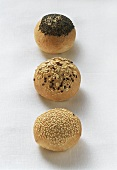 Three bread rolls with sesame, rolled oats and poppy seeds