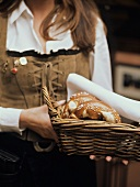 Woman in national dress serving bread basket with pretzels