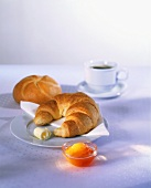 Breakfast of croissant, roll, jam and coffee