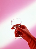 Hand in red rubber glove holding wine glass