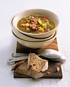 Hearty lentil soup with sausage; slices of bread