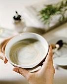 Hände halten grosse Tasse Milchkaffee