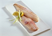 Two fresh redfish fillets garnished with lemon