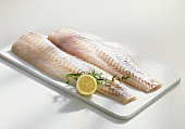 Two cod fillets on chopping board with lemon