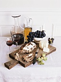 Still life with goat's cheese, raisin bread, grapes & red wine