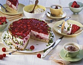 Raspberry cake with pistachios, pieces taken, and cappuccino