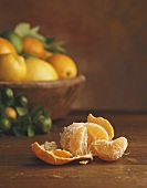 Peeled mandarin in front of basket of citrus fruit