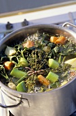 Vegetable broth with herbs in soup pot