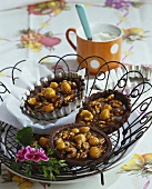 Chocolate tartlets with nuts in wire basket