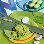 Place setting in spring colours with green candle