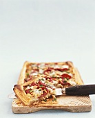 Onion pizza with sausage, blue cheese and pine nuts