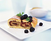 Piece of blackberry strudel with mint leaves