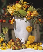 Autumnal flower arrangement with fruit in stone vase