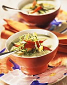 Cold cucumber soup, garnished with peppers and rocket