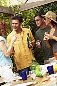 Two couples drinking wine at barbecue