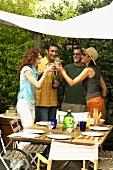 Two couples enjoying white wine at barbecue