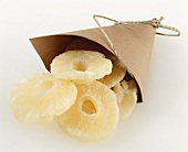 Candied pineapple slices in paper bag