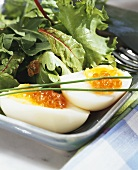 Boiled eggs with salmon caviare and salad leaves