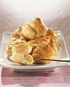 Profiteroles with cream filling, glazed with caramel