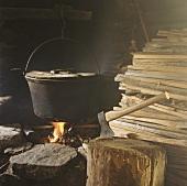 Kochtopf auf offenem Feuer, Axt und Holz in alter Hütte