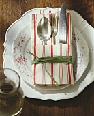 Place setting with cutlery in striped fabric napkin