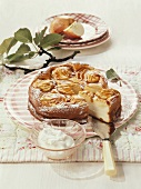 Apple cheesecake with icing sugar and cream