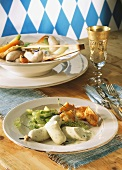 White sausages with zander, potato fritters & cucumber (Bavaria)