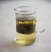 Grüner Tee mit Teeblättern im Glas