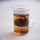 Schwarztee mit Teeblättern im Glas